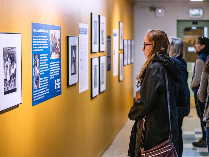 A young woman wearing a dark jacket and glasses reads a blue informational panel about an art exhibit on a yellow wall full of framed artwork.