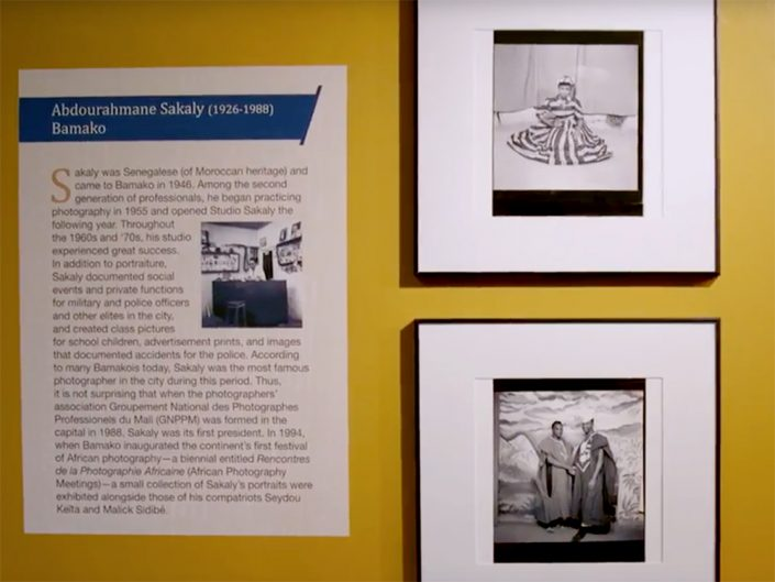 A yellow wall with black and white framed photos hung on it as well as a description of the photos.