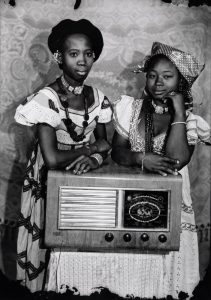 Black and white photo of two young women standing next to a vintage radio.