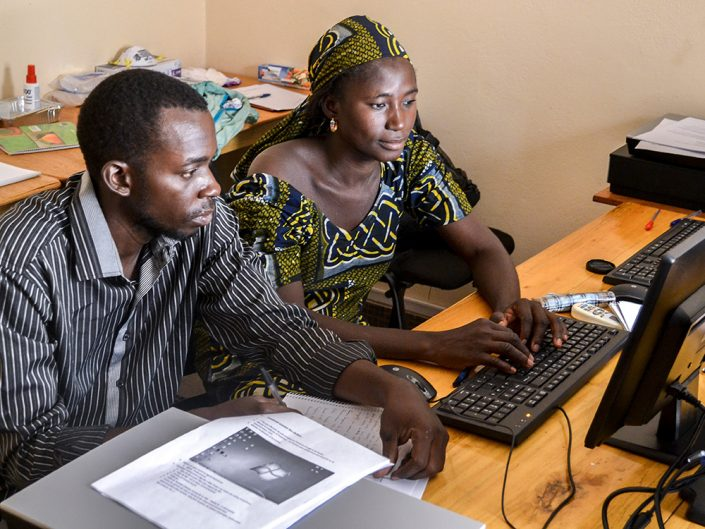 Two people sitting in front of a computer.