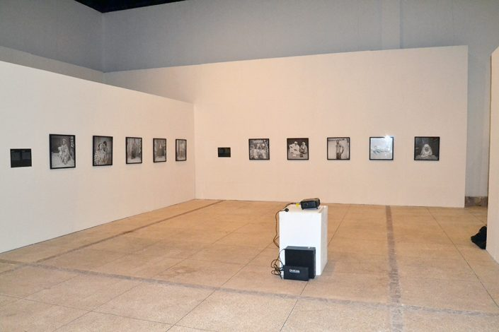 Black and white photos hung on white gallery walls.