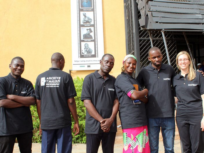 A group of people wearing black polo shirts standing in front of a banner advertising an art exhibit.