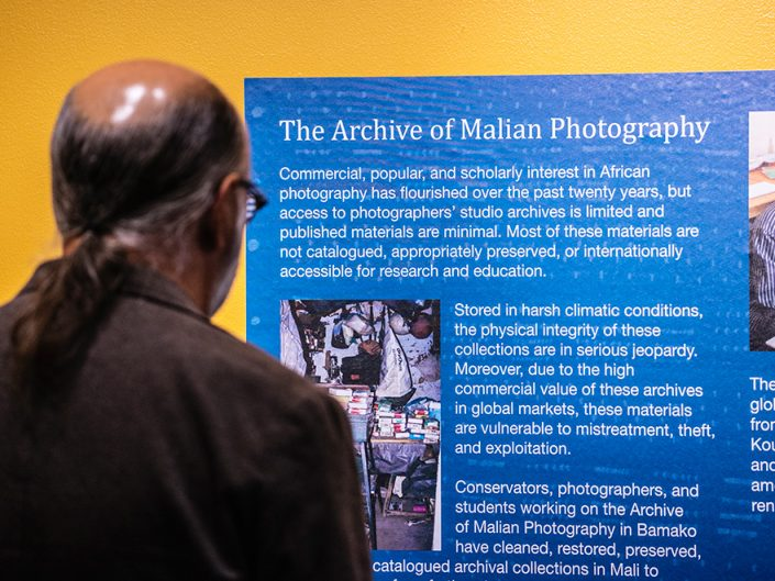 A man with a dark ponytail reads a blue informational panel about an art exhibit.