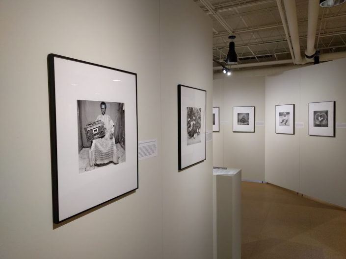 Art gallery with white walls with various black and white framed photos.